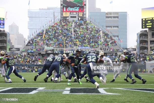 Russell Wilson hands the ball off to Chris Carson of the Seattle Seahawks in the first quarter during their game at CenturyLink Field on September 22...