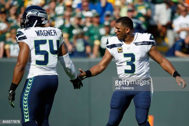 Russell Wilson high fives Bobby Wagner of the Seattle Seahawks during the first half against the Green Bay Packers at Lambeau Field on September 10...