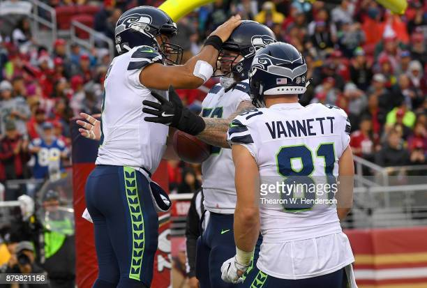Russell Wilson Justin Britt and Nick Vannett of the Seattle Seahawks celebrates after Wilson scored on a 2yard touchdown run against the San...