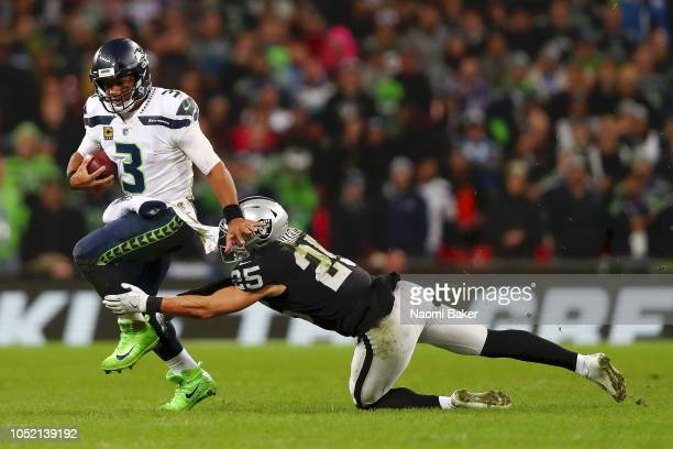 Russell Wilson of Seattle Seahawks is tackled by Erik Harris of Oakland Raiders during the NFL International series match between Seattle Seahawks...