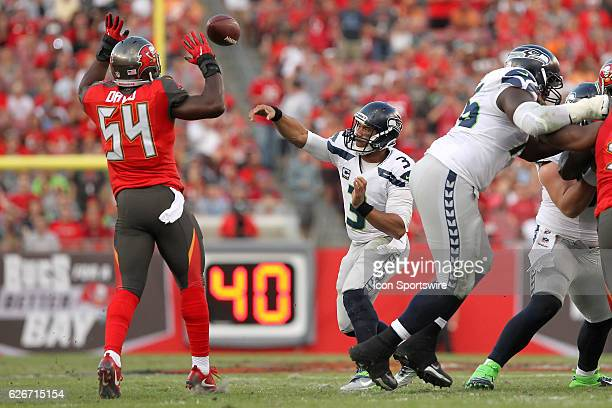 Russell Wilson of the Seahawks attempts to get a pass off over the Buccaneers Lavonte David during the NFL Game between the Seattle Seahawks and...