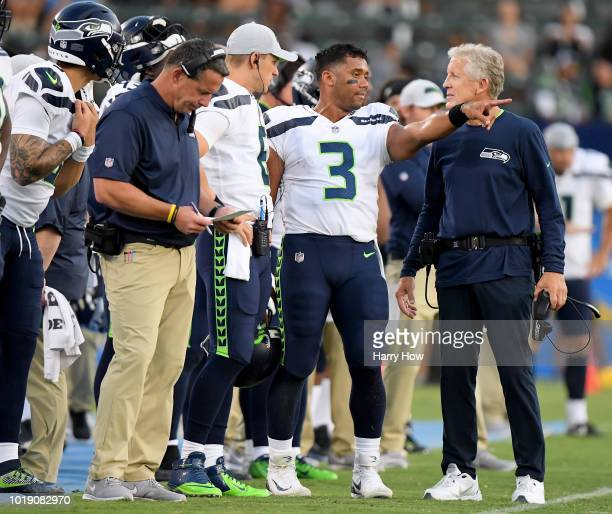 Russell Wilson of the Seattle Seahawks and head coach Pete Carroll talk on the sidelines during the first quarter of a presseason game against the...