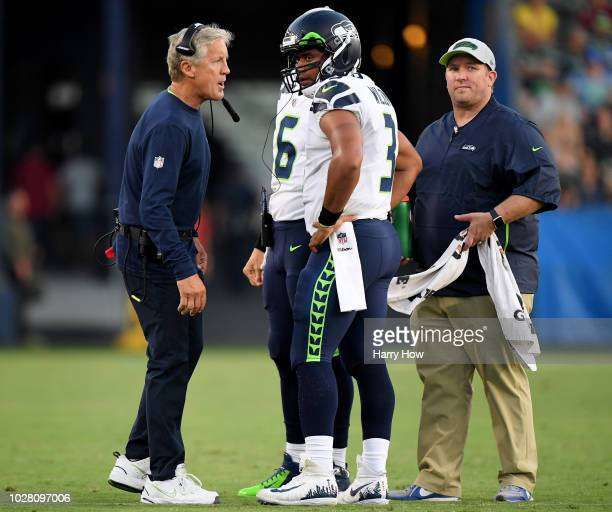 Russell Wilson of the Seattle Seahawks and head coach Pete Carroll talk during the first quarter of a presseason game against the Los Angeles...