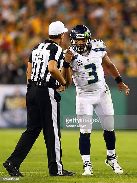 Russell Wilson of the Seattle Seahawks argues with referee Gene Steratore after a play against the Green Bay Packers during their game at Lambeau...