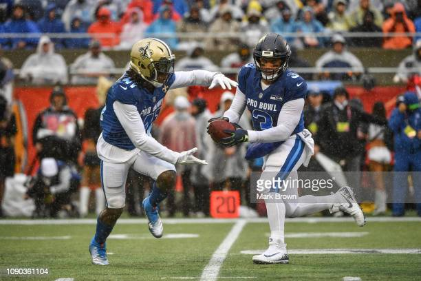 Russell Wilson of the Seattle Seahawks attempts a handoff to Alvin Kamara of the New Orleans Saints during the 2019 NFL Pro Bowl at Camping World...