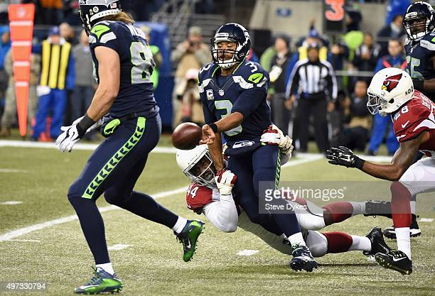 Russell Wilson of the Seattle Seahawks attempts to pitch the ball as he is tackled by Markus Golden of the Arizona Cardinals during the first half at...