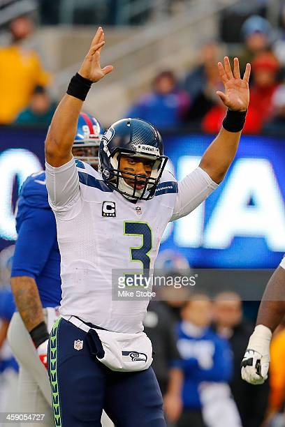 Russell Wilson of the Seattle Seahawks celebrates after throwing a touchdown against the New York Giants at MetLife Stadium on December 15, 2013 in...