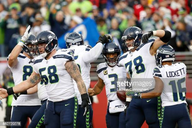 Russell Wilson of the Seattle Seahawks celebrates with teammates after scoring a touchdown against the San Francisco 49ers at Levi's Stadium on...