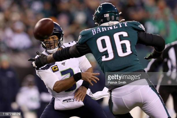 Russell Wilson of the Seattle Seahawks dishes off the ball under pressure from Derek Barnett of the Philadelphia Eagles in the first quarter during...