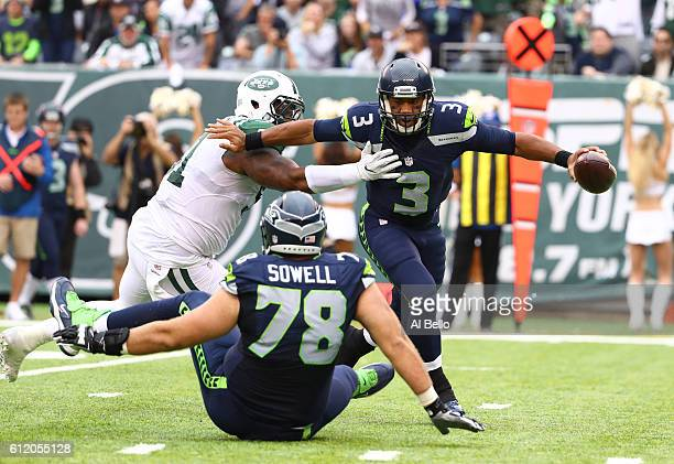 Russell Wilson of the Seattle Seahawks escapes the tackle of Sheldon Richardson of the New York Jets during their game at MetLife Stadium on October...