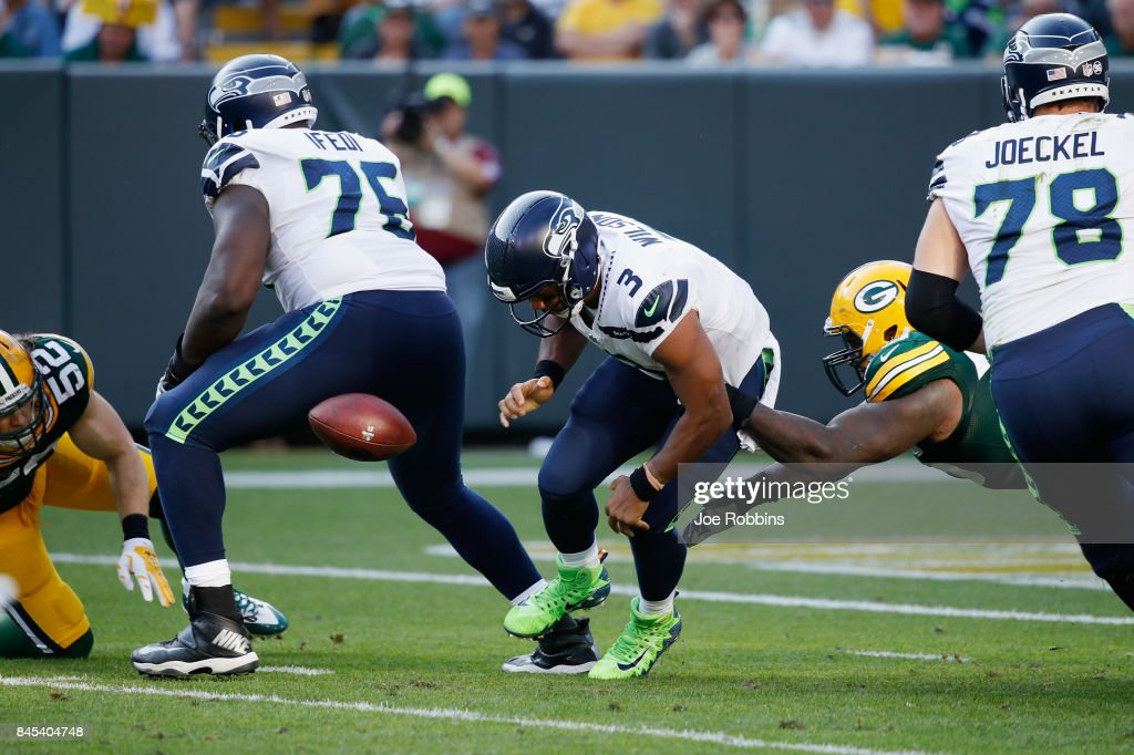 Russell Wilson #3 of the Seattle Seahawks fumbles the football as he is hit by Mike Daniels #76 of the Green Bay Packers during the third quarter at Lambeau Field on September 10, 2017 in Green Bay, Wisconsin.