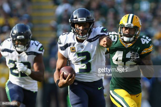 Russell Wilson of the Seattle Seahawks gestures as he runs with the ball during the second quarter against the Green Bay Packers at Lambeau Field on...