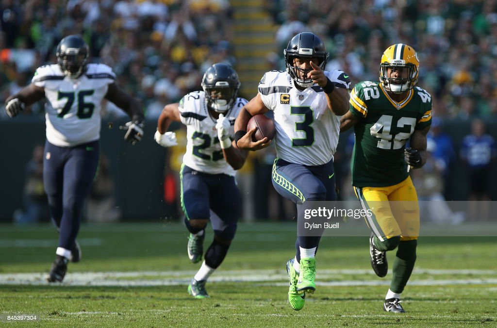 Russell Wilson #3 of the Seattle Seahawks gestures as he runs with the ball during the second quarter against the Green Bay Packers at Lambeau Field on September 10, 2017 in Green Bay, Wisconsin.