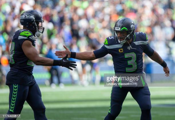 Russell Wilson of the Seattle Seahawks greets Bobby Wagner in the fourth quarter against the Cincinnati Bengals at CenturyLink Field on September 8,...