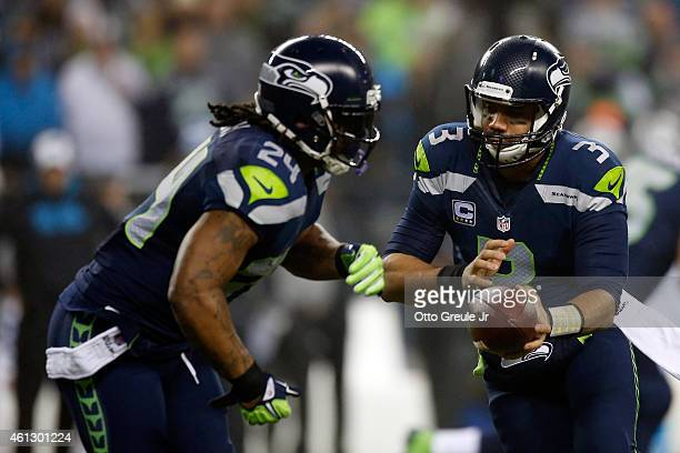 Russell Wilson of the Seattle Seahawks hands off the ball to Marshawn Lynch in the first quarter against the Carolina Panthers during the 2015 NFC...