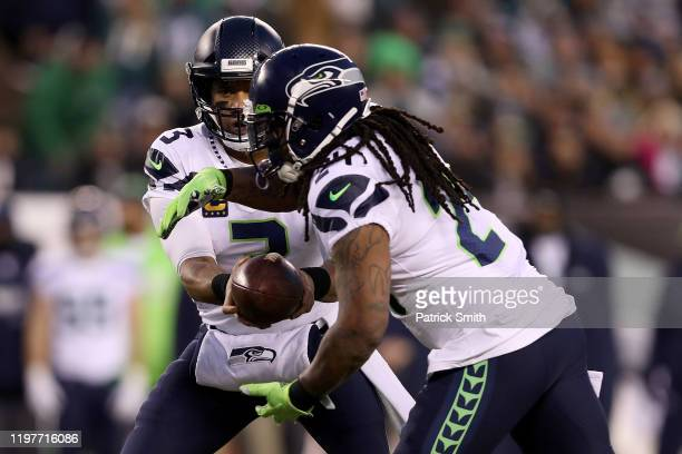 Russell Wilson of the Seattle Seahawks hands off to Marshawn Lynch against the Philadelphia Eagles in the first quarter during their NFC Wild Card...