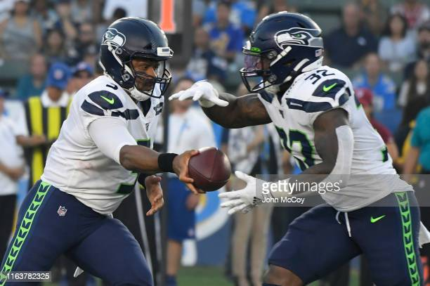 Russell Wilson of the Seattle Seahawks hands the ball off to Chris Carson of the Seattle Seahawks in the first half of a preseason NFL football game...
