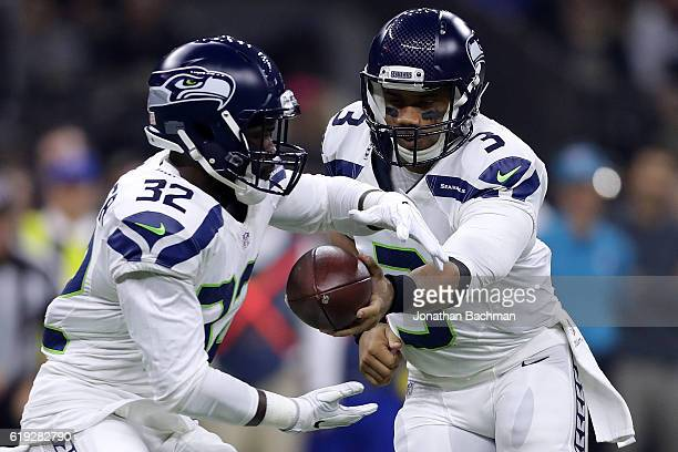 Russell Wilson of the Seattle Seahawks hands the ball to Christine Michael of the Seattle Seahawks during the first half of a game against the New...