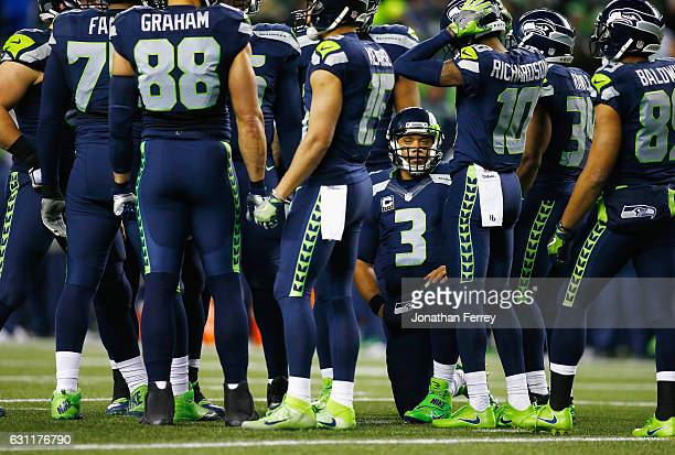 Russell Wilson of the Seattle Seahawks huddles with teammates during the first half against the Detroit Lions in the NFC Wild Card game at...