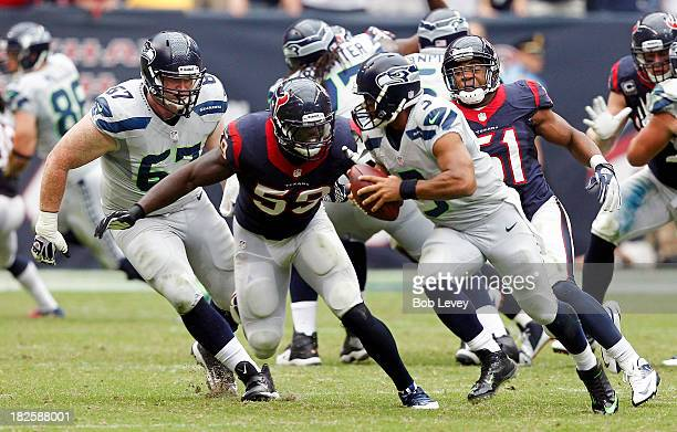Russell Wilson of the Seattle Seahawks is pursued by Whitney Mercilus of the Houston Texans and Darryl Sharpton of the Houston Texans at Reliant...