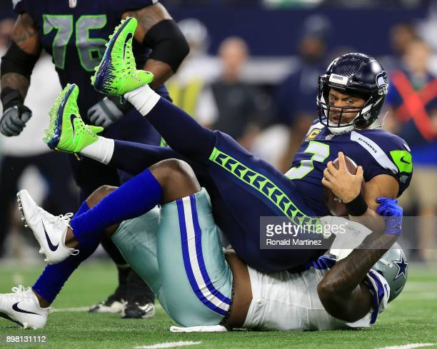 Russell Wilson of the Seattle Seahawks is sacked by Benson Mayowa of the Dallas Cowboys in the first half of a football game at AT&T Stadium on...