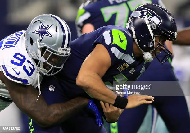 Russell Wilson of the Seattle Seahawks is sacked by Benson Mayowa of the Dallas Cowboys at AT&T Stadium on December 24, 2017 in Arlington, Texas.