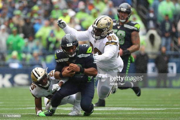 Russell Wilson of the Seattle Seahawks is tackled by Eli Apple and Malcom Brown of the New Orleans Saints in the second quarter during their game at...