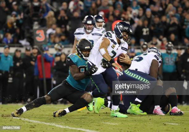 Russell Wilson of the Seattle Seahawks is tackled by Yannick Ngakoue of the Jacksonville Jaguars during the second half of their game at EverBank...