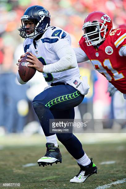 Russell Wilson of the Seattle Seahawks is tackled from behind by Tamba Hali of the Kansas City Chiefs at Arrowhead Stadium on November 16 2014 in...