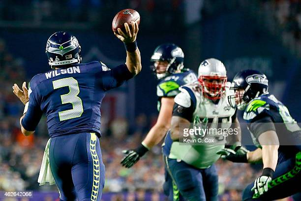 Russell Wilson of the Seattle Seahawks looks to pass in the fourth quarter against the New England Patriots during Super Bowl XLIX at University of...