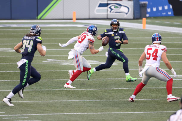 Russell Wilson of the Seattle Seahawks looks to throw the ball while being pressured by Carter Coughlin of the New York Giants in the third quarter...