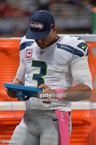 Russell Wilson of the Seattle Seahawks on the sidelines reviewing strategy on his Microsoft Surface Pro tablet during a game against the St Louis...