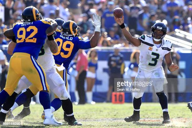 Russell Wilson of the Seattle Seahawks passes as Tanzel Smart and Aaron Donald of the Los Angeles Rams defend during the second half of a game at Los...