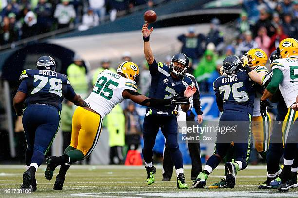 Russell Wilson of the Seattle Seahawks passes the ball as Datone Jones of the Green Bay Packers applies pressure during the second half of the 2015...