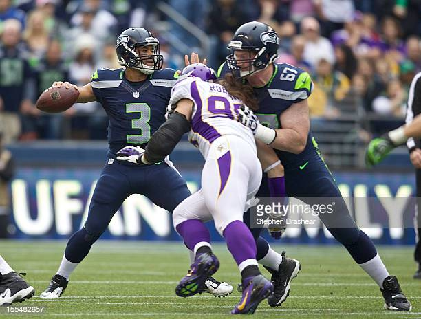 Russell Wilson of the Seattle Seahawks passes the ball as Paul McQuistan of the Seattle Seahawks blocks Brian Robison of the Minnesota Vikings during...