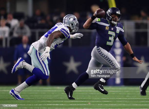Russell Wilson of the Seattle Seahawks passes the ball under pressure from Randy Gregory of the Dallas Cowboys in the second quarter during the Wild...