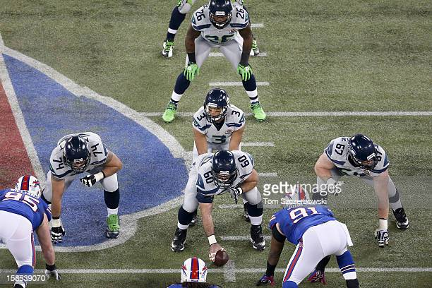 Russell Wilson of the Seattle Seahawks prepares for the snap from Max Unger as John Moffitt and Paul McQuistan line up on the offensive line and...
