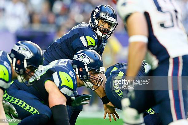 Russell Wilson of the Seattle Seahawks prepares for the snap in the first quarter against the New England Patriots during Super Bowl XLIX at...
