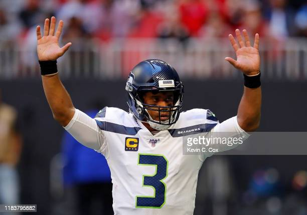 Russell Wilson of the Seattle Seahawks reacts after passing for a touchdown in the first half against the Atlanta Falcons at Mercedes-Benz Stadium on...
