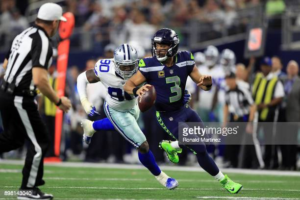 Russell Wilson of the Seattle Seahawks runs away from DeMarcus Lawrence of the Dallas Cowboys in the second half at ATT Stadium on December 24 2017...