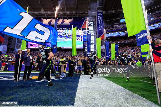 Russell Wilson of the Seattle Seahawks runs onto the field with his teammates prior to Super Bowl XLIX against the New England Patriots at University...