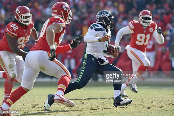 Russell Wilson of the Seattle Seahawks runs the ball against Josh Mauga Dontari Poe and Tamba Hali of the Kansas City Chiefs during the game at...