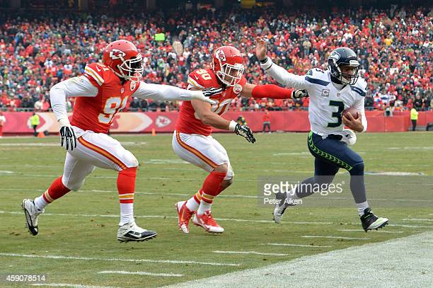 Russell Wilson of the Seattle Seahawks runs the ball against Tamba Hali and Josh Mauga of the Kansas City Chiefs during the first half at Arrowhead...