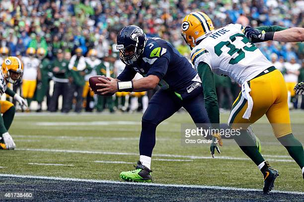 Russell Wilson of the Seattle Seahawks runs the ball in for a touchdown as Micah Hyde of the Green Bay Packers closes in during the fourth quarter of...