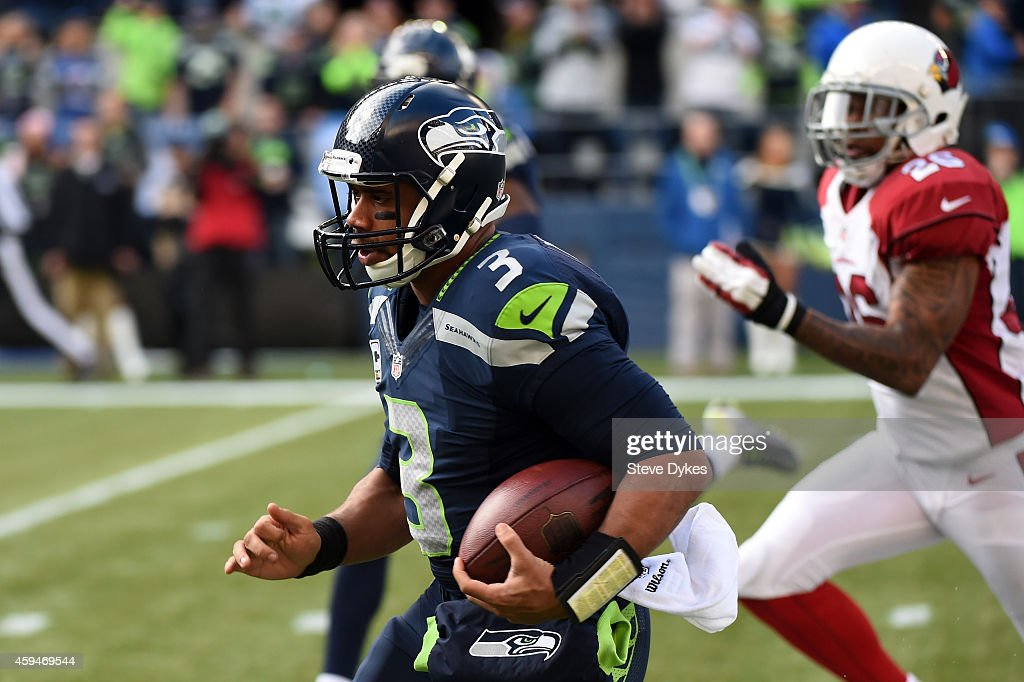 Russell Wilson #3 of the Seattle Seahawks runs the ball in the first half against the Arizona Cardinals during their game at CenturyLink Field on November 23, 2014 in Seattle, Washington.