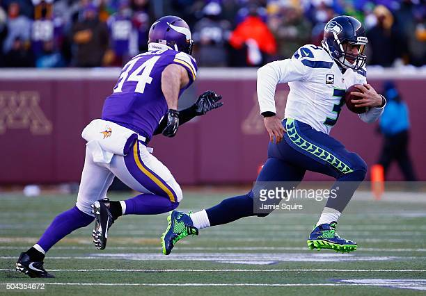 Russell Wilson of the Seattle Seahawks runs with the ball as Andrew Sendejo of the Minnesota Vikings defends him in the second quarter during the NFC...