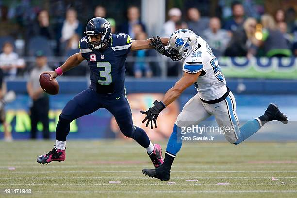 Russell Wilson of the Seattle Seahawks runs with the ball as Travis Lewis of the Detroit Lions defends during the first half at CenturyLink Field on...