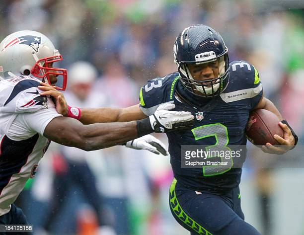 Russell Wilson of the Seattle Seahawks rushes the ball against the Jerod Mayo of the New England Patriots during a game at CenturyLink Field on...