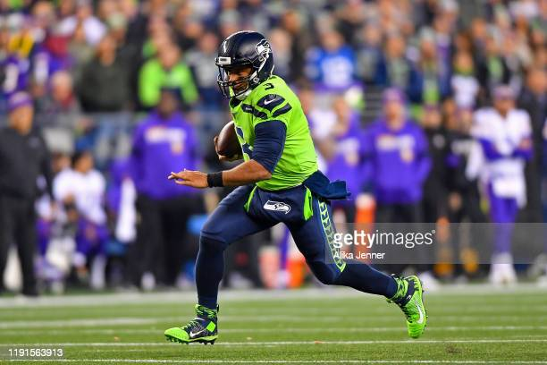 Russell Wilson of the Seattle Seahawks scrambles for yardage during the first quarter against the Minnesota Vikings at CenturyLink Field on December...