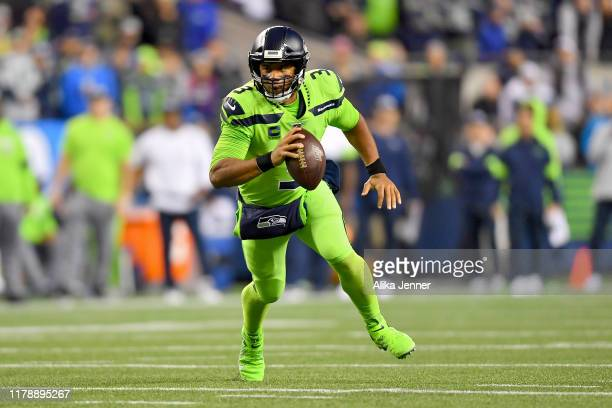 Russell Wilson of the Seattle Seahawks scrambles out of the pocket during the game against the Los Angeles Rams at CenturyLink Field on October 03...